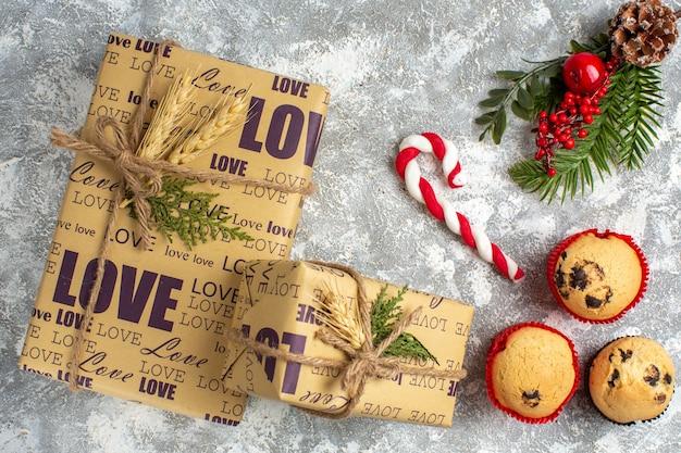 Bovenaanzicht van kleine cupcakes, snoep en dennentakken, decoratieaccessoires, coniferenkegel en geschenken op ijsoppervlak