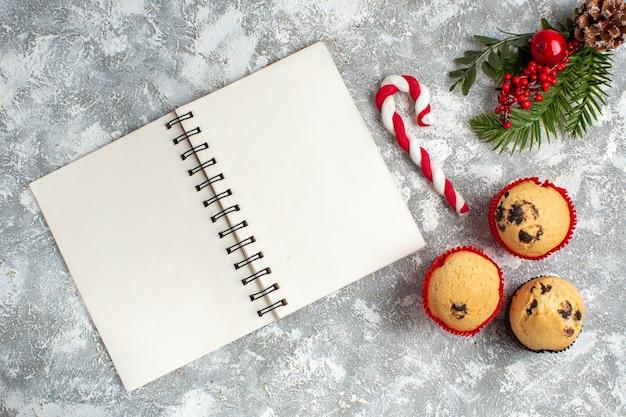 Bovenaanzicht van kleine cupcakes, snoep en dennentakken, decoratieaccessoires, coniferenkegel en notitieboekje op ijsoppervlak
