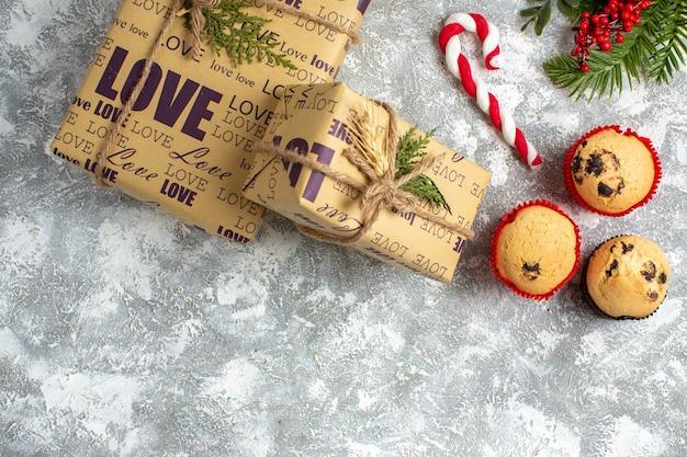 Bovenaanzicht van kleine cupcakes, snoep en dennentakken, decoratieaccessoires en geschenken op ijsoppervlak