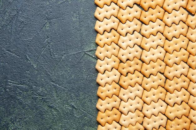 Bovenaanzicht van kleine gezouten crackers op donkere ondergrond