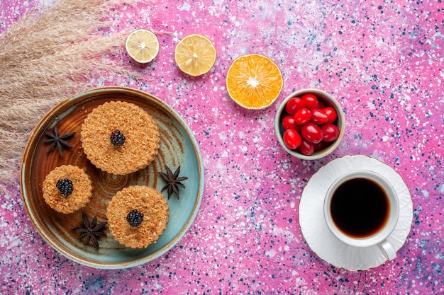 Bovenaanzicht van kleine heerlijke taarten met kornoelje en thee op het lichtroze oppervlak