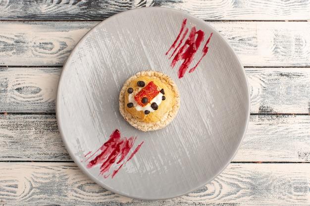 Bovenaanzicht van kleine heerlijke taarten met roomfruit en marmelade bovenop