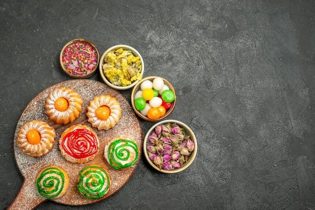 Bovenaanzicht van kleine heerlijke taarten met snoepjes en bloemen op zwart