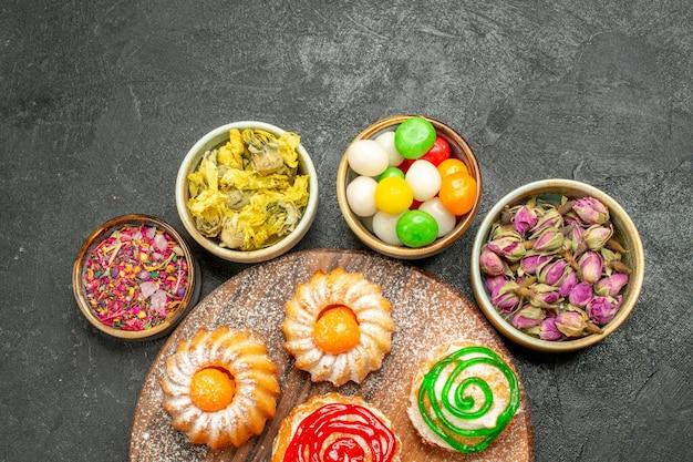 Bovenaanzicht van kleine heerlijke taarten met snoepjes en bloemen op zwart Gratis Foto