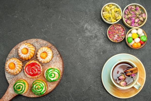 Bovenaanzicht van kleine heerlijke taarten met snoepjes, thee en bloemen op zwart