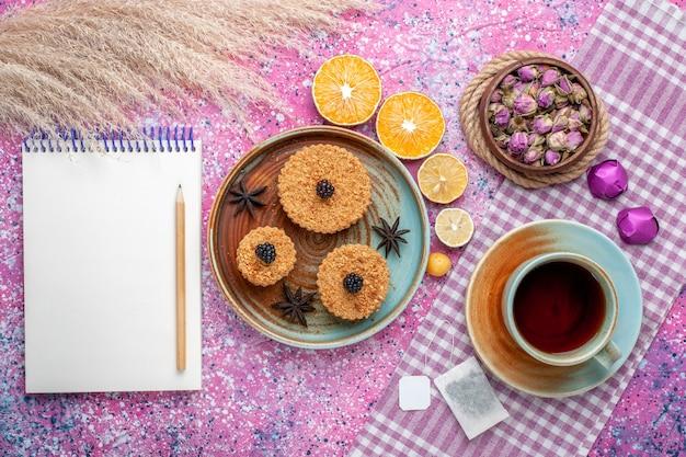 Bovenaanzicht van kleine heerlijke taarten met stukjes sinaasappel en thee op het lichtroze oppervlak