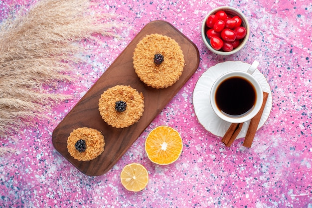 Bovenaanzicht van kleine heerlijke taarten ronde gevormd met kaneel en thee op het lichtroze oppervlak