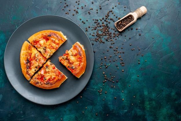 Bovenaanzicht van kleine kaas pizza vier gesneden binnen plaat met peper op donkerblauw oppervlak