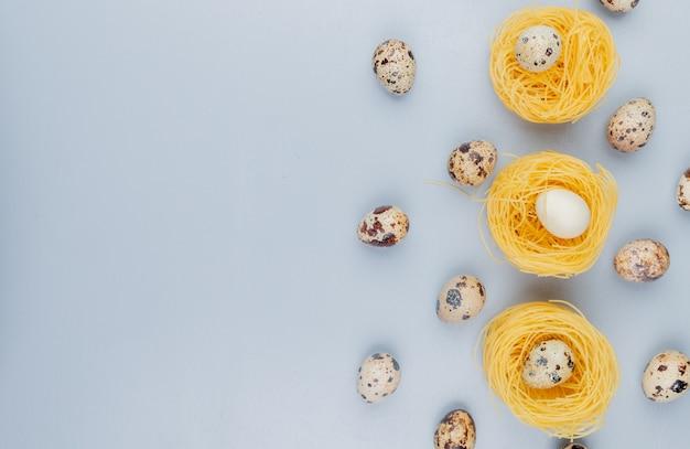 Bovenaanzicht van kleine kwarteleitjes met crème gekleurde schelpen op een nest op een witte achtergrond met kopie ruimte