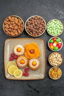 Bovenaanzicht van kleine lekkere taarten met snoep, fruit en noten op grijs