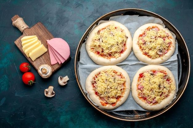 Bovenaanzicht van kleine rauwe pizza's deeg met groenten en kaas in pan op het donkerblauwe oppervlak
