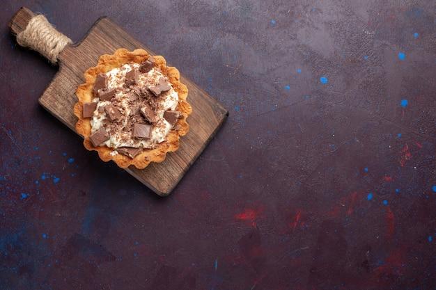 Bovenaanzicht van kleine romige cake met chocoladestukjes op het donkere oppervlak
