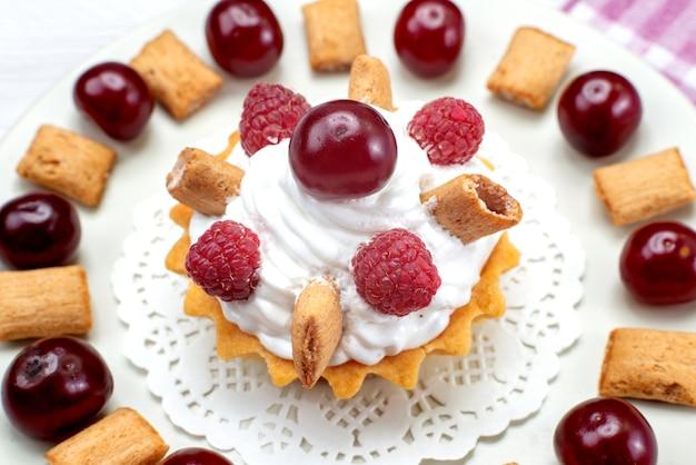 Bovenaanzicht van kleine romige cake met frambozen en kleine koekjes op wit-licht bureau