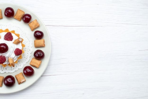 Bovenaanzicht van kleine romige cake met frambozen en kleine koekjes op wit
