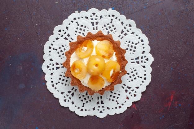 Bovenaanzicht van kleine romige cake met gesneden fruit op het donkere oppervlak