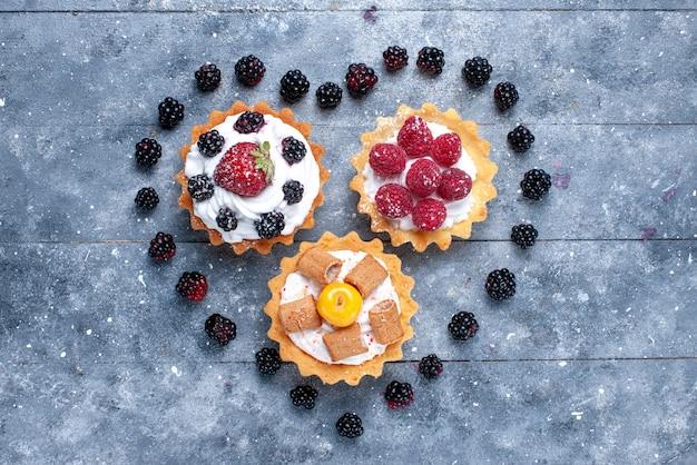 Bovenaanzicht van kleine romige cakes met frambozen en hartvormige bramen op de heldere foto van het koekje van de fruitbessencake