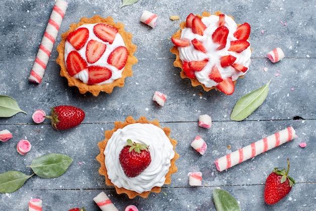 Bovenaanzicht van kleine romige cakes met gesneden en verse aardbeien samen met stoksnoepjes op grijs