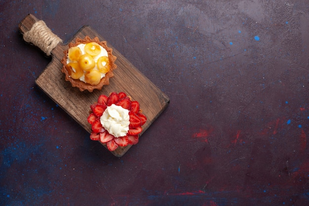 Bovenaanzicht van kleine romige cakes met gesneden fruit op een donkere ondergrond