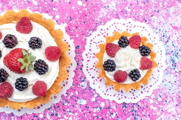 Bovenaanzicht van kleine romige taarten met verschillende bessen op licht wit