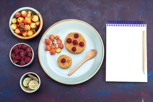 Bovenaanzicht van kleine ronde cake met verse frambozen in plaat met fruit op het donkere oppervlak