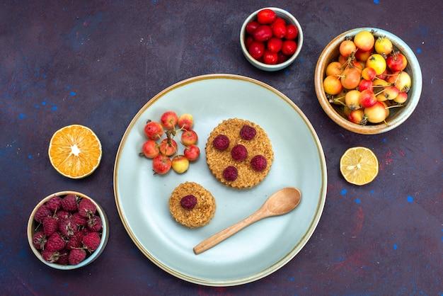 Bovenaanzicht van kleine ronde cake met verse frambozen in plaat met vers fruit op donkere ondergrond