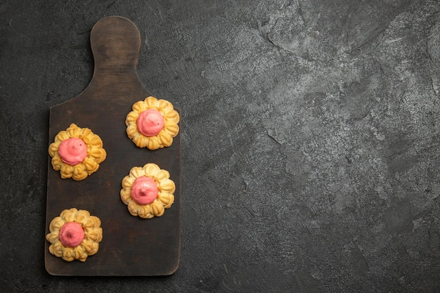 Bovenaanzicht van kleine suikerkoekjes met aardbeienroom op het grijze oppervlak