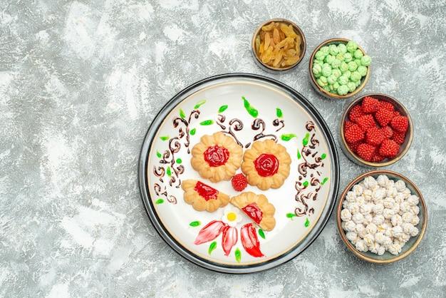 Bovenaanzicht van kleine suikerkoekjes met snoepjes op wit