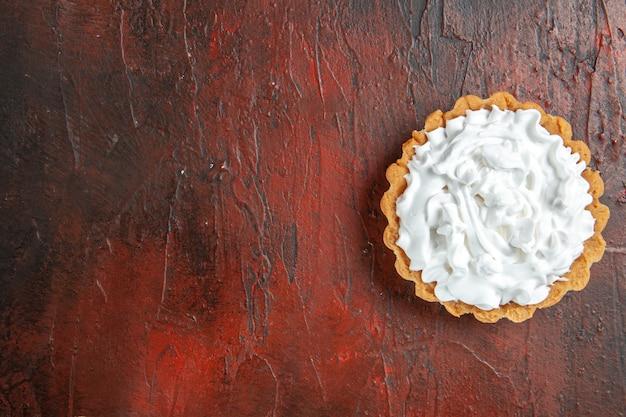 Bovenaanzicht van kleine taart met banketbakkersroom op donkerrood oppervlak