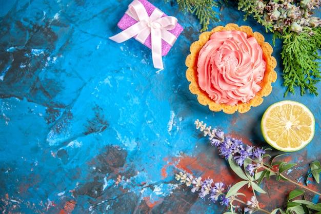 Bovenaanzicht van kleine taart met roze banketbakkersroom citroenschijfje op blauwe ondergrond