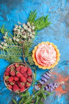 Bovenaanzicht van kleine taart met roze banketbakkersroom kom met frambozen op blauwe ondergrond
