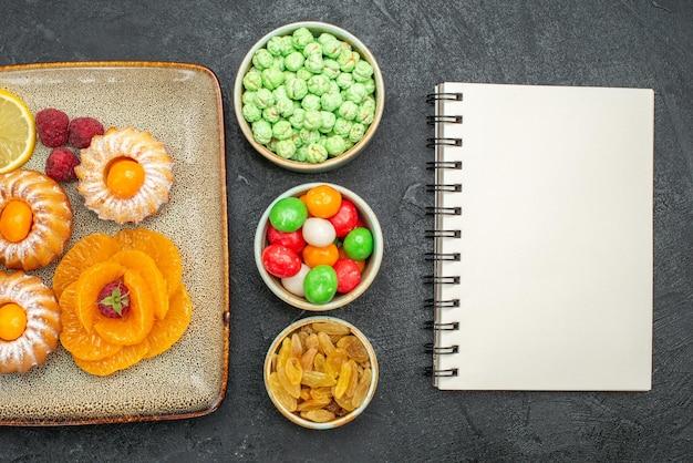 Bovenaanzicht van kleine taarten met schijfjes citroen, mandarijnen en snoepjes op zwarte tafel