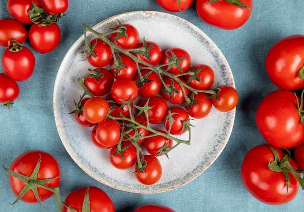 Bovenaanzicht van kleine tomaten in plaat met andere op blauw