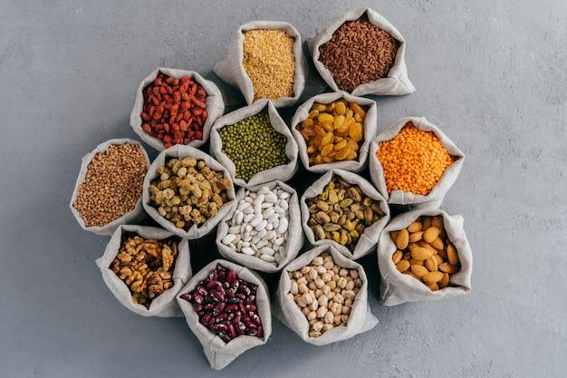 Bovenaanzicht van kleine zakjes met granen: boekweit, linzen, haricot, kikkererwten, goji, rozijnen, pistache
