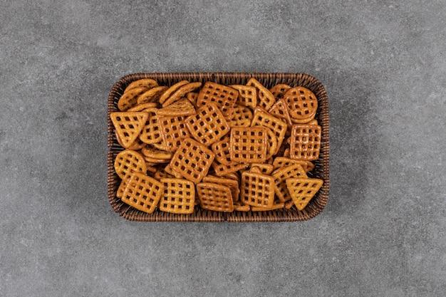 Bovenaanzicht van kleine zelfgemaakte koekjes in mand over grijze tafel.