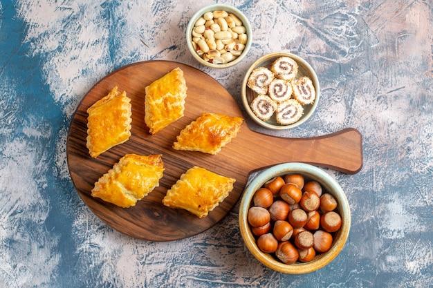 Bovenaanzicht van kleine zoete gebakjes met noten op blauwe ondergrond