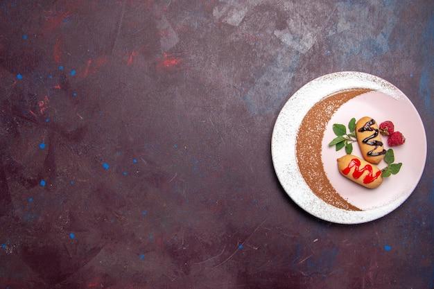 Bovenaanzicht van kleine zoete koekjes in een ontworpen bord op zwart paars