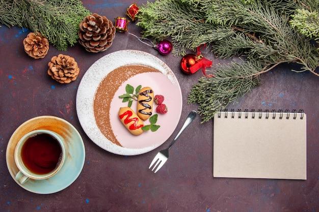 Bovenaanzicht van kleine zoete koekjes in ontworpen bord op zwarte tafel