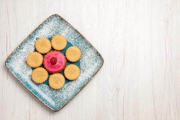 Bovenaanzicht van kleine zoete koekjes met fruitcake in plaat op witte tafel