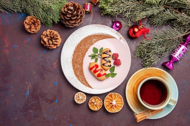 Bovenaanzicht van kleine zoete koekjes met kopje thee op zwart