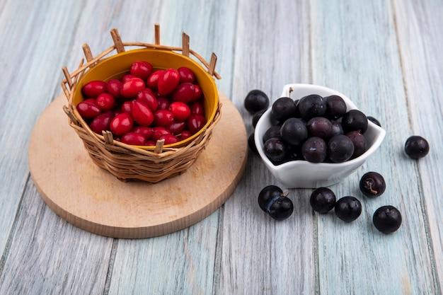Bovenaanzicht van kleine zure sleedoorn op een witte kom met rode cornel bessen op een emmer op een houten keukenbord op een grijze houten achtergrond