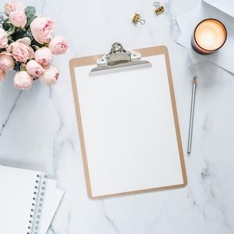 Bovenaanzicht van klembord met witte lege pagina. klembord, bloemen, geurkaars op wit marmer.