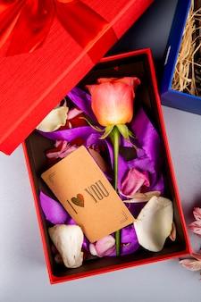 Bovenaanzicht van kleur kleur roze bloem met paars lint en kleine bruine papieren kaart in een rode huidige doos op witte tafel