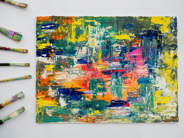 Bovenaanzicht van kleurrijk schilderij met borstels