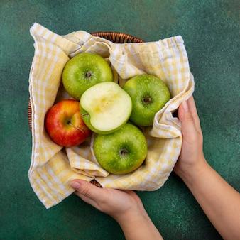 Bovenaanzicht van kleurrijke appels op emmer versierd met geruit tafelkleed op groen