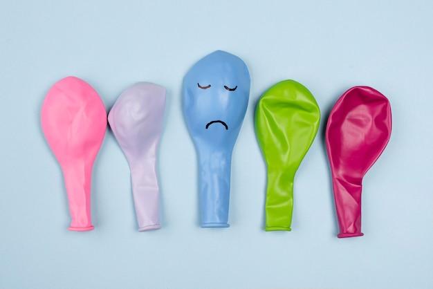 Bovenaanzicht van kleurrijke ballonnen met frons voor blauwe maandag