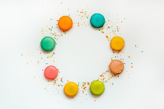 Bovenaanzicht van kleurrijke bitterkoekjes en hagelslag gerangschikt in cirkel op witte achtergrond. kopieer ruimte.