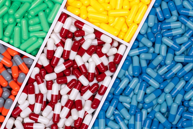 Bovenaanzicht van kleurrijke capsule pillen in plastic bakje.