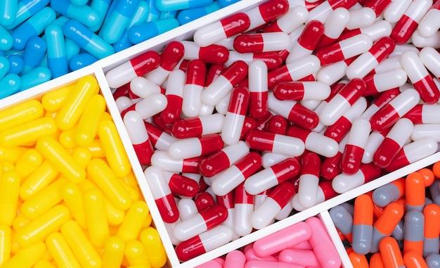 Bovenaanzicht van kleurrijke capsulepillen in plastic bakje. farmaceutische industrie. gezondheidszorg en medicijnen. geneesmiddelenproductie. farmaceutisch concept. vitaminen en supplementencapsules. heldere kleurencapsule.