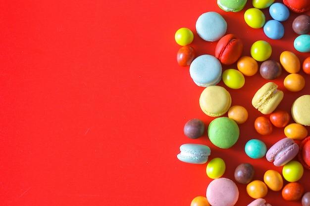 Bovenaanzicht van kleurrijke chocoladesuikergoed en macarons op rode achtergrond met kopieerruimte