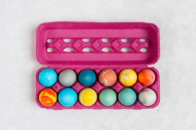 Bovenaanzicht van kleurrijke eieren voor pasen in karton